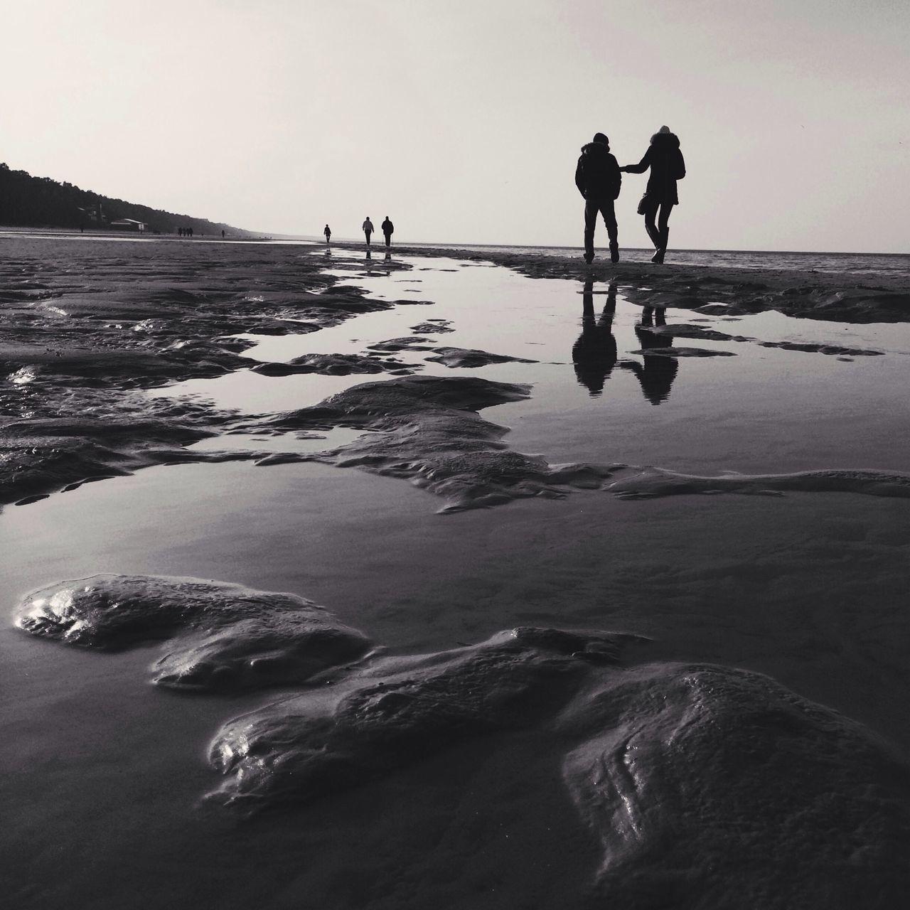 Group of people walking on beach