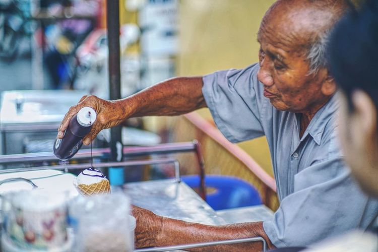 Side view of mature man making ice cream