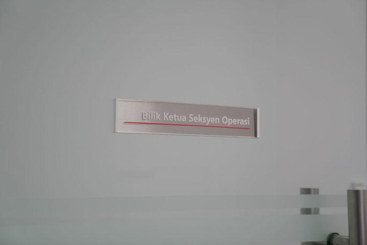 Low angle view of information sign against wall