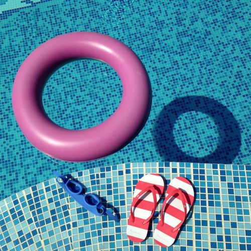 High angle view of inflatable ring in pool by swimming goggles and footwear