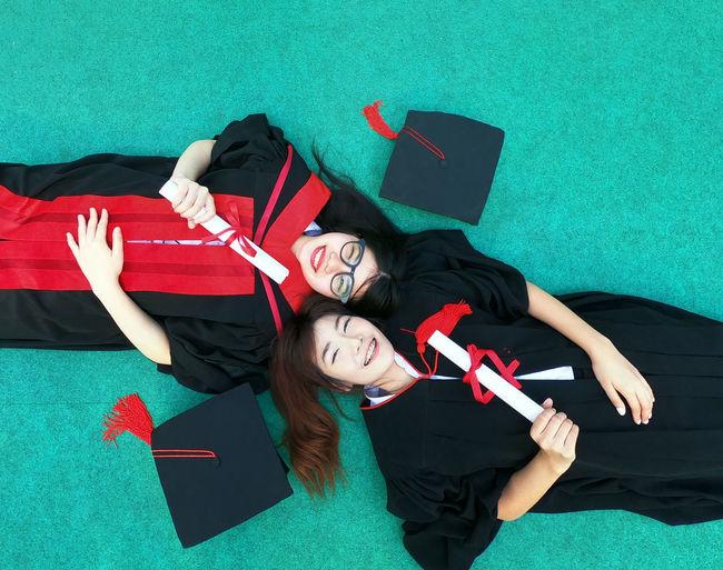 Portrait of friends in graduation gowns lying on floor