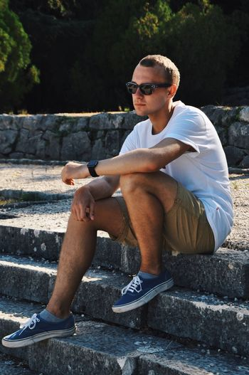 Young man sitting on retaining wall