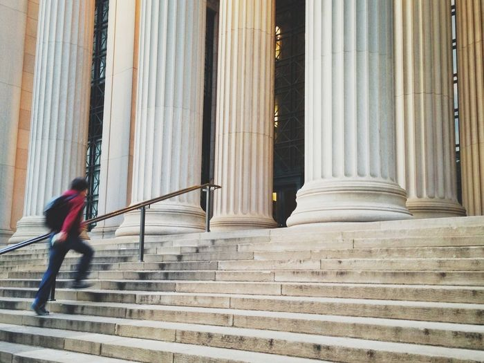 Side view of blurred man walking up building front stairs