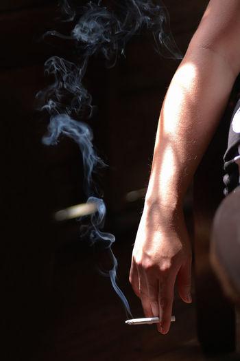 Cropped image of man holding burning cigarette