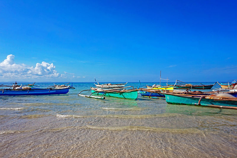 Beach Boats Beauty In Nature Blue Boat Colorful Fishing Boat Day Eyeem Philippines Fishing Boats Mode Of Transport Moored Nature Nautical Vessel No People Outdoors Sailboat Scenics Sea Shore Sky Sunny The Week On EyeEm Tranquil Scene Tranquility Transportation Water My Commute