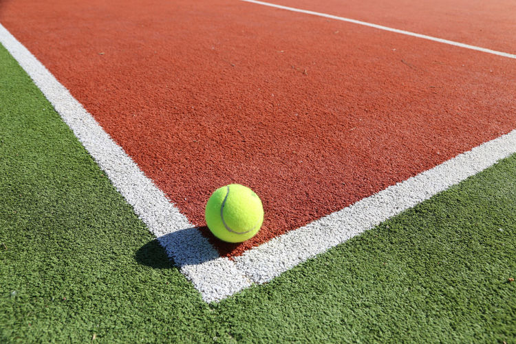 Ball Close-up Court Day Dividing Line Grass High Angle View Leisure Activity No People Outdoors Playing Field Racket Sport Shadow Sport Sports Equipment Sports Venue Tennis Tennis Ball