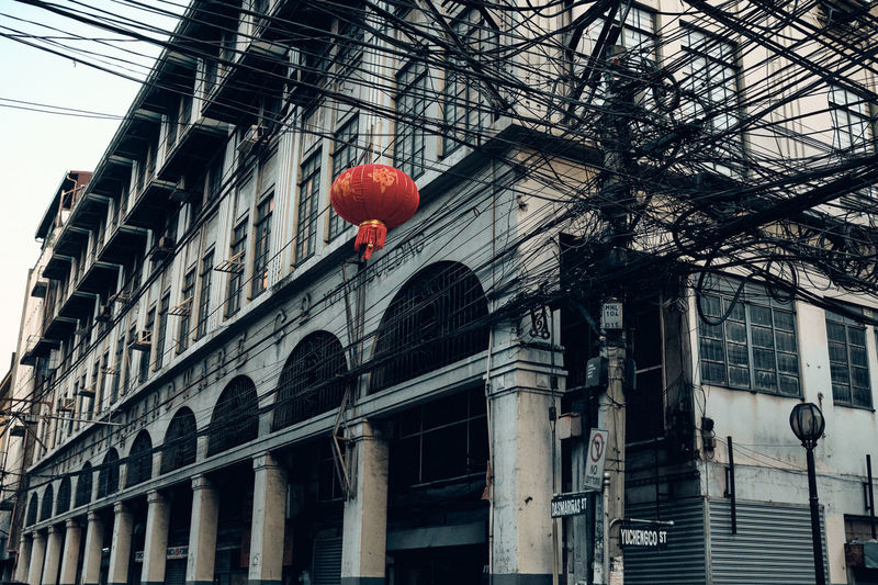 Low angle view of red lanterns hanging on street by building