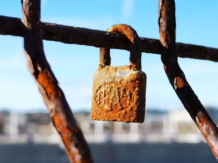 Close-up of padlock on fence against sky