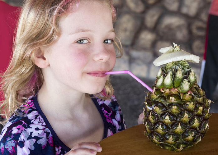 A young girl enjoys a piña colada from a pineapple at a roadside cafe in Cuba. Cuba Pineapple Sipping Blond Hair Drink Drinking Fancy Food And Drink Fruit Girl Headshot Looking At Camera One Person Piña Piña Colada Portrait Real People Straw Tourism Tropical Vacation Been There.