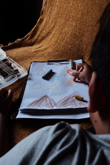 Midsection of kid drawing random stuff in paper on table