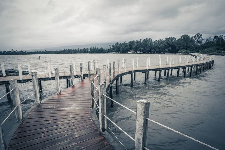 Empty wooden pier on sea against sky