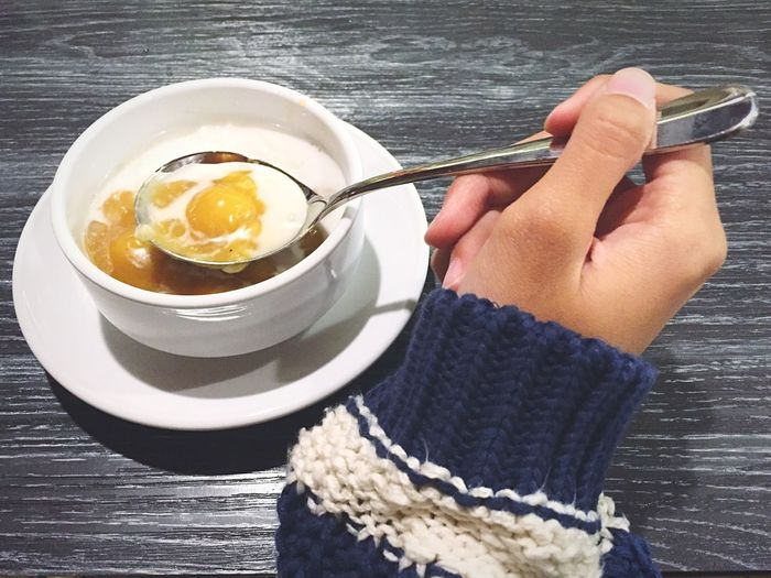 Cropped Woman Hand With Porridge In Bowl On Table