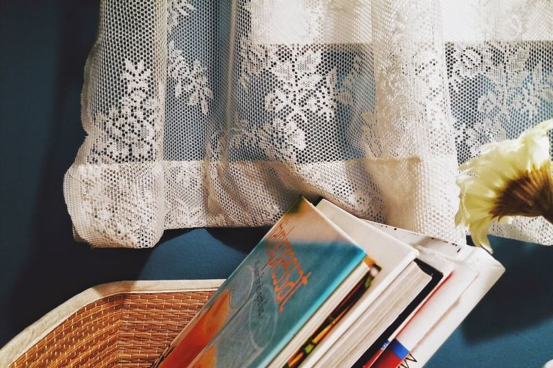 Close-up of books in wicker basket against wall
