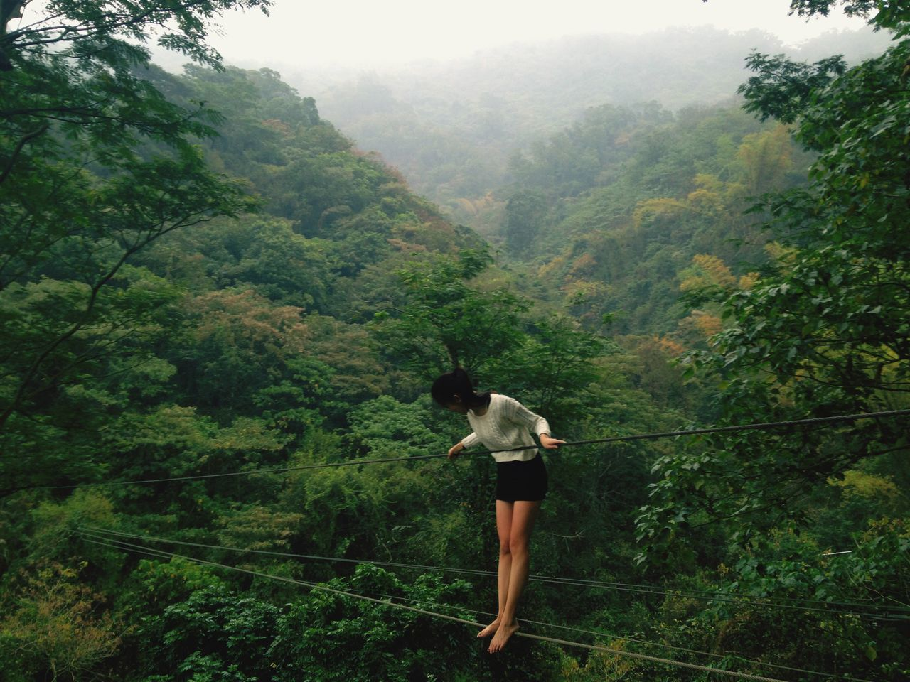 Full length of young woman standing on rope in forest