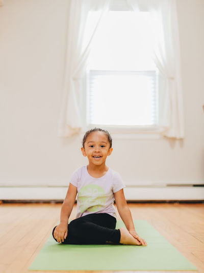 Portrait of smiling girl sitting on wooden floor