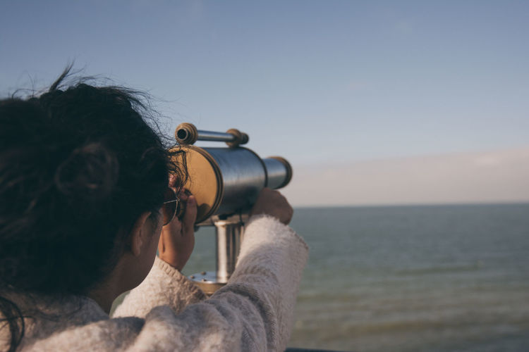Woman Looking Through Coin-Operated Binoculars At Sea Against Sky