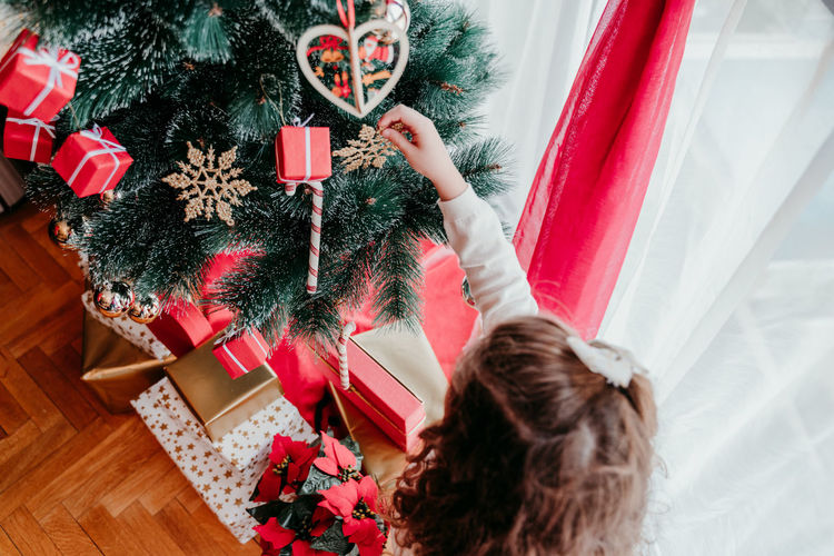 High angle view of girl decorating christmas tree at home