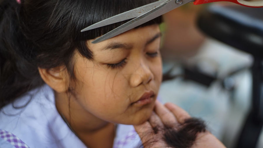 Cropped hand cutting girl hair outdoors