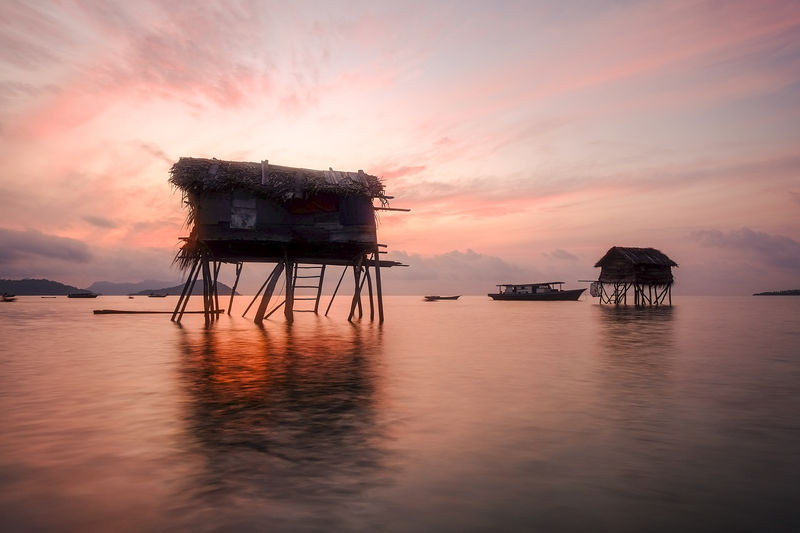 Stilt structures at calm sea against scenic sky