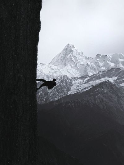Silhouette man climbing on rocky mountain against clear sky