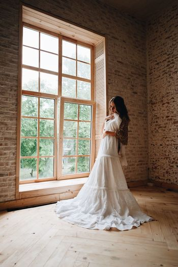 Woman Holding Wedding Dress While Standing Against Wall