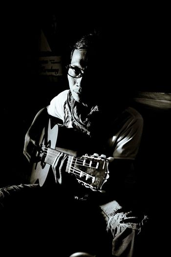 Play Guitar EyeEm Indonesia Accoustic Guitar Guitar One Person Sitting Indoors  Real People Front View Young Adult Adult Portrait Dark Shadow Arts Culture And Entertainment Lifestyles Leisure Activity High Angle View Three Quarter Length Looking Away Men Black Background