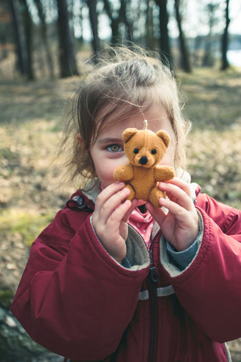 Portrait of girl holding teddy bear while standing on field