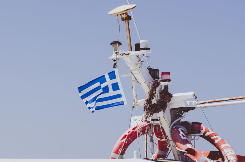 Low angle view of flag on nautical vessel against sky