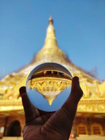 Midsection of person holding crystal ball against pagoda