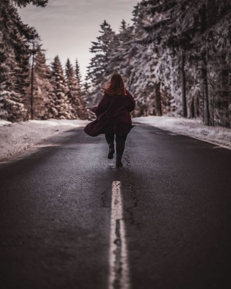 Rear view of woman walking on road amidst trees during winter