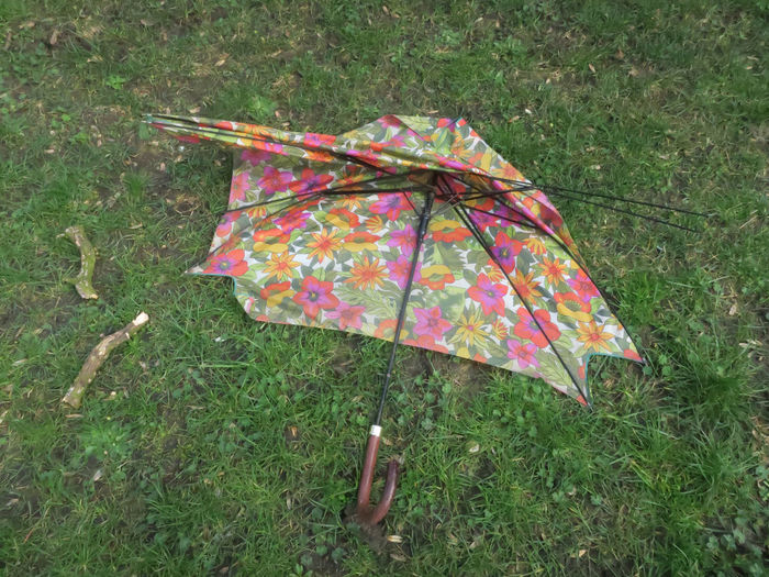 broken umbrella with floral pattern Grass Field Umbrella Nature Protection Day High Angle View Outdoors Green Color No People Floral Pattern Water Rainy Days Rain