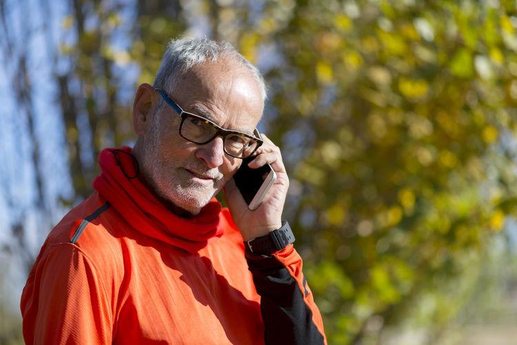Portrait of senior man talking on mobile phone against trees