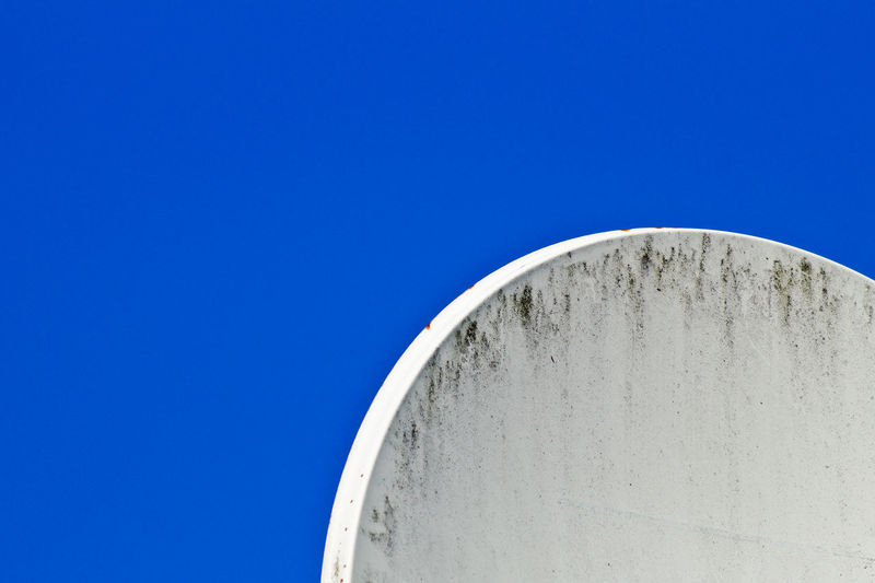 Cropped image of satellite dish against clear blue sky