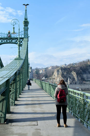 Architecture Bridge - Man Made Structure Building Exterior Built Structure Casual Clothing Connection Day Footbridge Full Length Leisure Activity Lifestyles Men Nature Outdoors People Real People Rear View Sky The Way Forward Travel Destinations Two People Walking Women