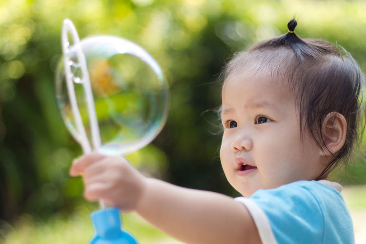 Close-up of cute girl making bubble with wand