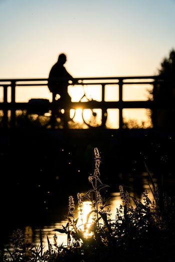 Silhouette man standing on bridge over lake against sky during sunset