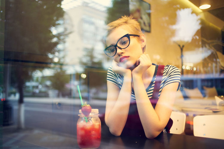 Young woman looking away while sitting by table at cafe