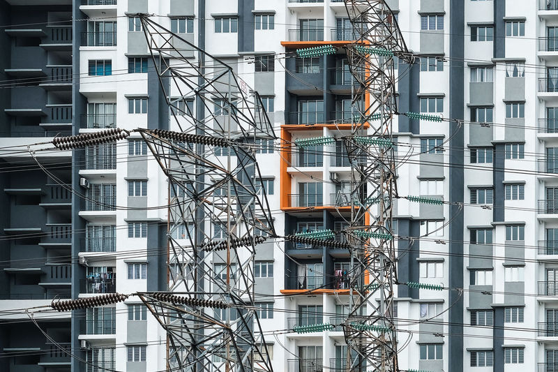 Low Angle View Of Electricity Pylons Against Building In City