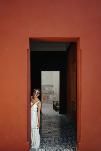 Woman wearing sunglasses standing by doorway