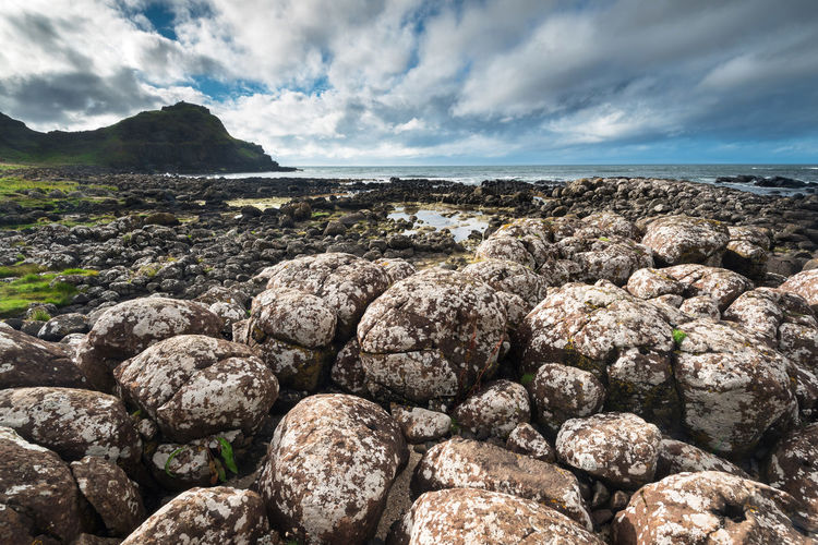 View of rocky beach against cloudy sky