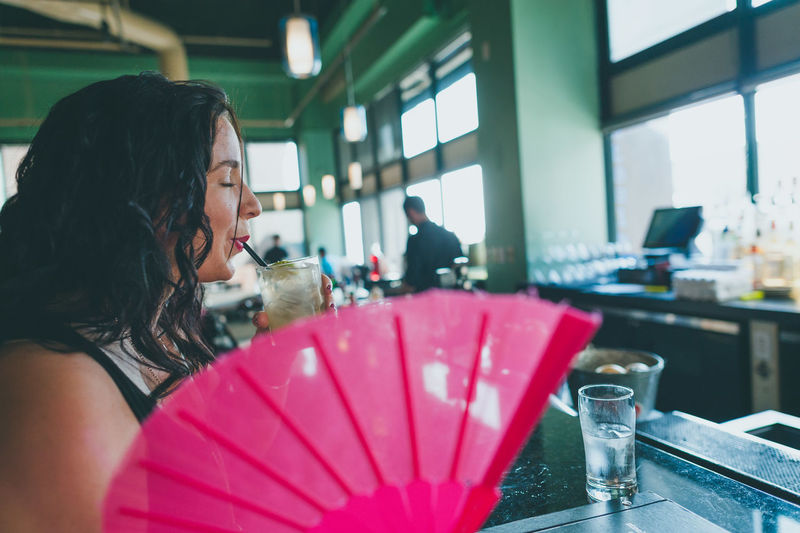 Side view of young woman drinking beverage at table in restaurant