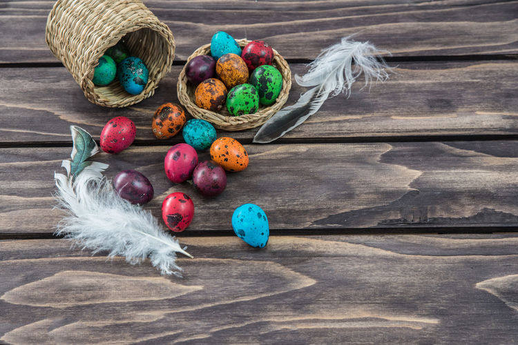 High Angle View Of Easter Eggs With Feathers And Wicker Baskets On Table