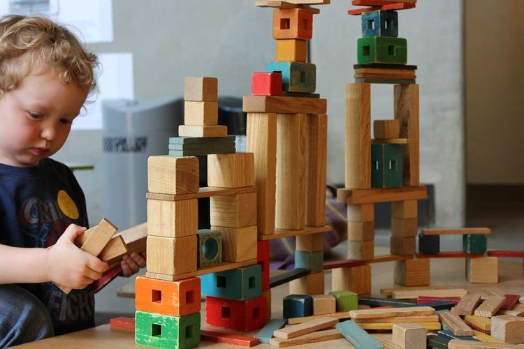 toddler playing with colorful toy blocks Boys Casual Clothing Child Childhood Concentration Creativity Holding Indoors  Innocence Large Group Of Objects Leisure Activity Males  Men Multi Colored One Person Playing Real People Toy Toy Block Wood - Material Inner Power