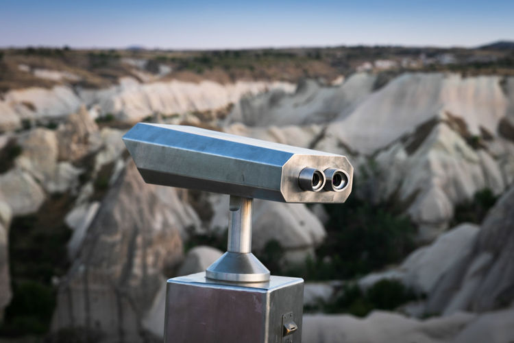 Close-up of coin-operated binoculars on rock