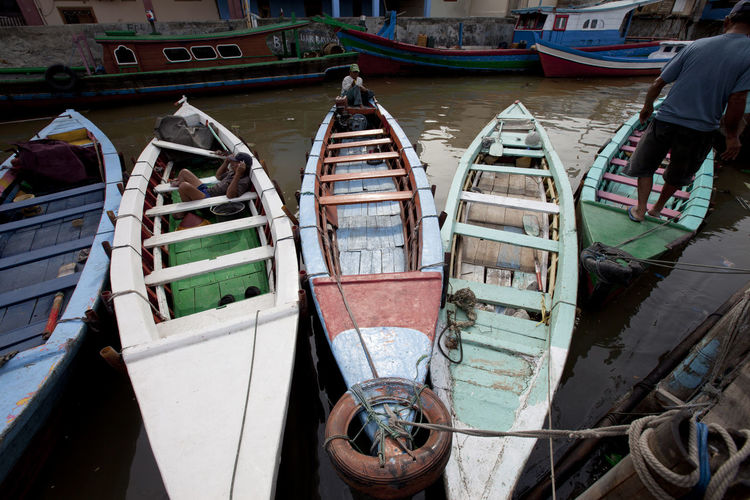 People in boats moored at canal