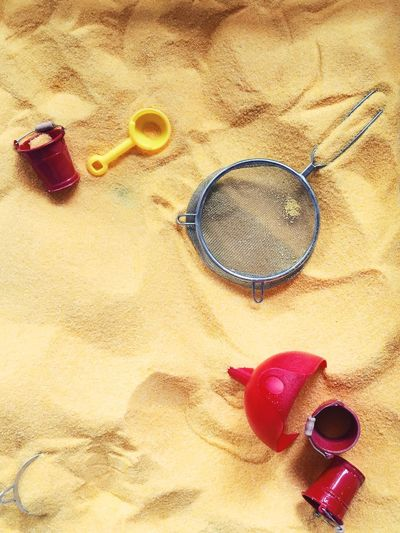 Directly above shot of strainer and plastic toys on sandy beach