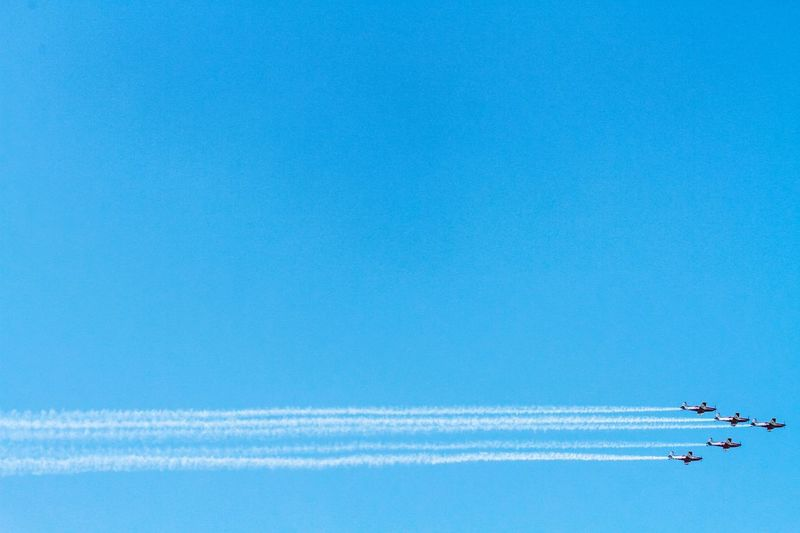 Low angle view of airplanes flying against clear blue sky