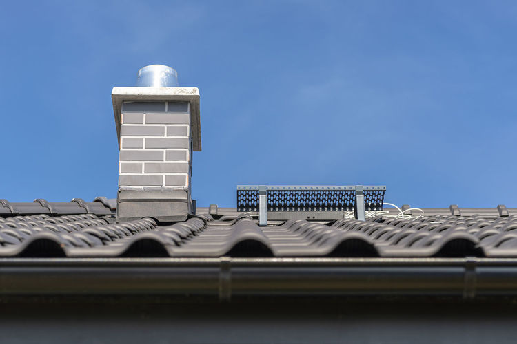 The roof of a single-family house covered with a new ceramic tile in anthracite, system chimneny.