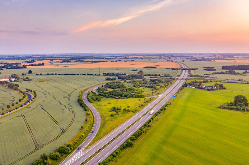 High angle view of road amidst field against sky during sunset