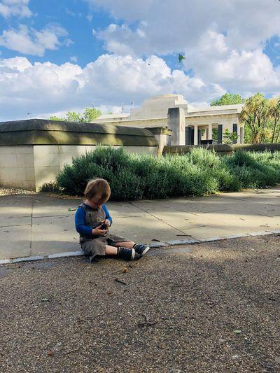 Boy sitting on building against sky